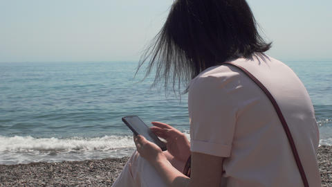 Woman Sitting Near The Sea Relaxing And Using Smartphone Archivo