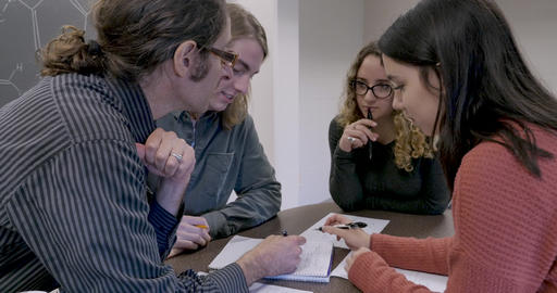 Male professor teaching science to a small group of students in a classroom using pen and paper Footage
