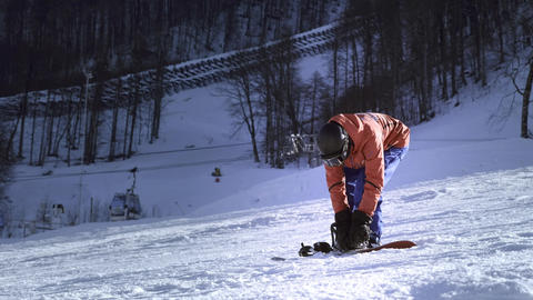 Professional rider puts snowboard on his feet. Button fasteners. Getting ready Footage