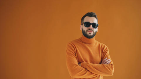 Portrait of confident bearded guy in sunglasses standing with asrms crossed Live Action