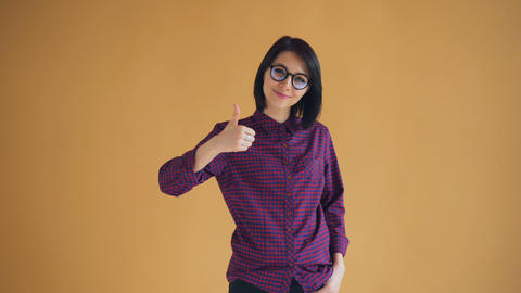 Portrait of happy girl with black hair showing thumbs-up smiling recommending Footage