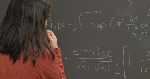 Young woman in her 20s or late teens thinking about a complicated problem on a chalkboard Footage