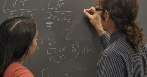 Man and young woman working and collaborating together on a complicate problem on a chalkboard Live Action