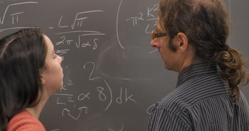 Two scientists or mathematicians agreeing on a solution to a complex problem written on a blackboard Live Action