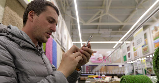 Man taking photo in household section of hypermarket Footage