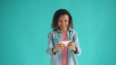 Portrait of female mixed race student playing game on smartphone holding gadget Live Action