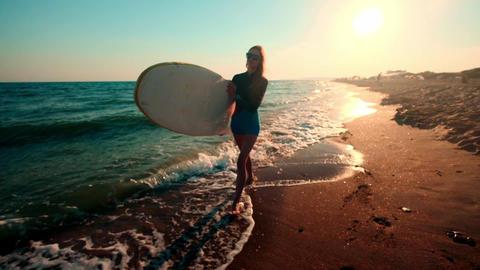 SLOW MOTION: Beautiful slim girl walking on the beach, holding surfboard. Runs Footage