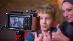 Shot in camera lens of joyful small boy and his muslim mother in hijab recording Footage