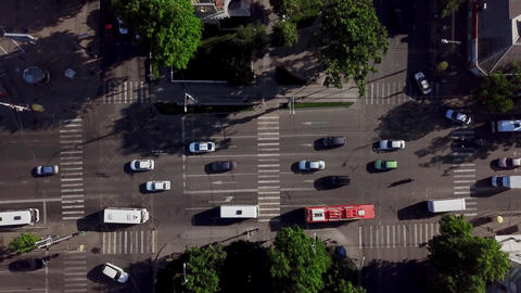 Drone's Eye View - Aerial view of the vehicular intersection, fly under trees Footage