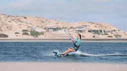 Young Woman Kiteboarding to Shore and Sitting on Sand Live Action
