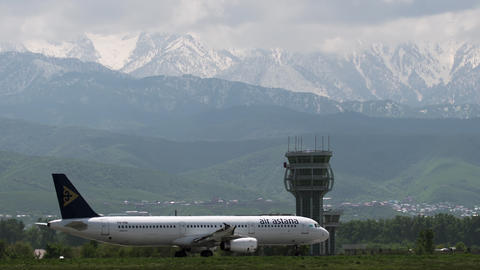 Commercial jet of Air Astana taxiing against mountains Live Action