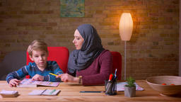 Muslim mother in hijab learning letters with her small son at the table at home Footage