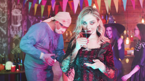 Young woman dressed in a vampire costume drinks blood at a halloween party Footage
