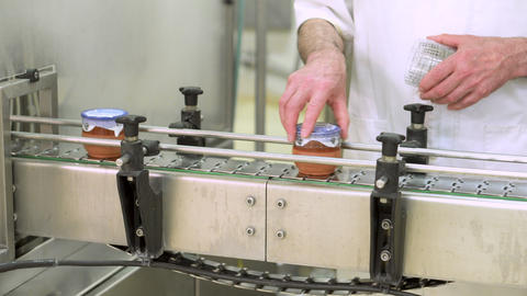 Operator sealing product at final Stage of Production Yogurt-Filling. Premium Live Action