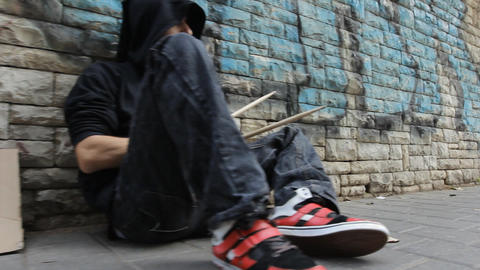 A homeless street performer person drum by the sidewalk Stock Video Footage