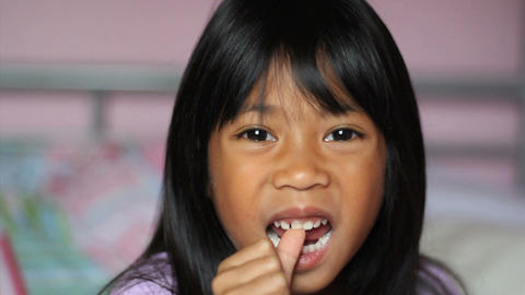 Asian Girl Wiggling Her First Loose Tooth stock footage