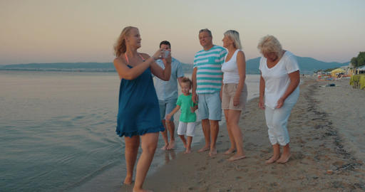 Big family walking on beach and taking pictures Footage