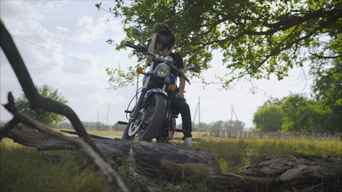 A man on a motorbike against the sea. Motorcyclist stands under a tree Archivo