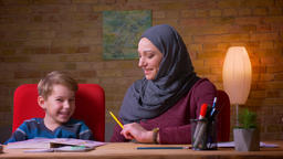 Close-up shot of muslim mother in hijab learning letters with her small son at Footage
