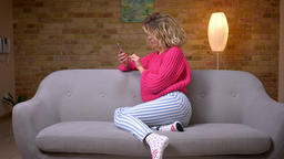 Blonde housewife in pink sweater sitting in profile on... Stock Video Footage