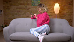 Blonde housewife in pink sweater sitting in profile on sofa surfing in Footage