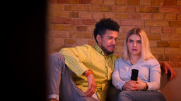 Dolly shot of young african guy with his blonde caucasian girlfriend watching TV Footage