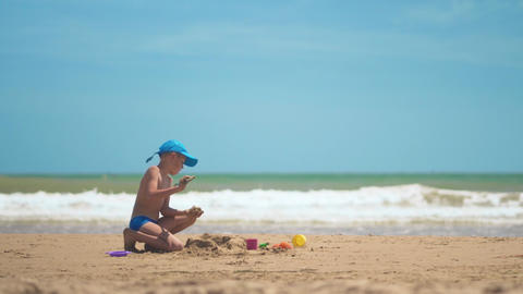 A little boy is playing in the sand on the sea, little legs and fingers, a Live Action