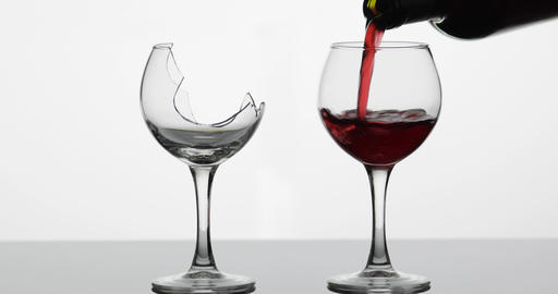 Wine. Red wine pouring into normal and broken wine glasses on the wet surface Footage
