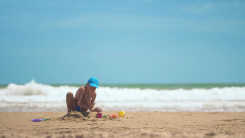 A little boy is playing in the sand on the sea, little legs and fingers, a Footage
