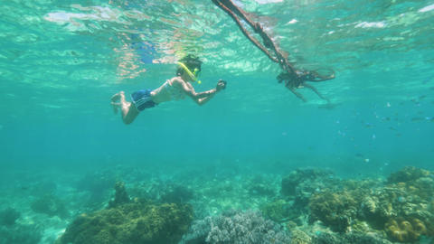 Snorkeling teen girl is taking a pictures of sea life on…, Live Action