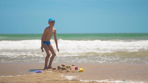A little boy is playing in the sand on the sea, little…, Live Action