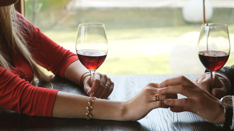 Close up of loving couple holding hands and clinking glasses of red wine during Archivo