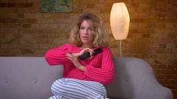 Blonde housewife in pink sweater on sofa watching TV shows tender emotions and Footage