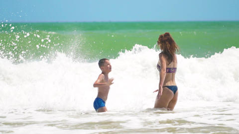 mother and son jump into the sea on the waves, rejoise, have fun Archivo