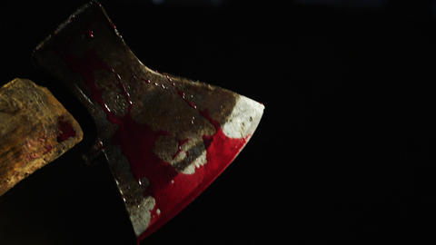 Axe with blood in hand on the dark background. Close-up shot Footage