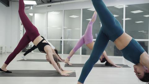 [alt video] Yoga students are practicing Warrior pose Virabhadrasana...