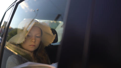 Girl Reading Book Inside Car in backseat Archivo