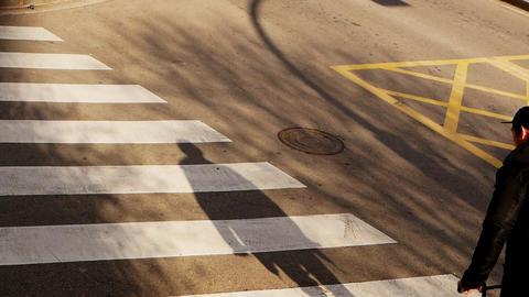 Slim teenage boy bicyclist is slowly riding on concrete flat ground in street Footage