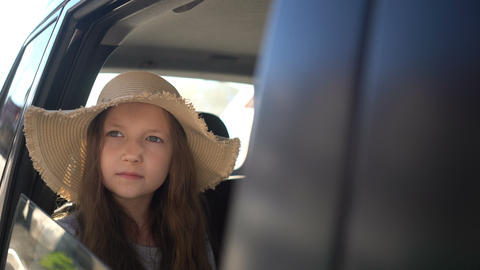 Happy beautiful girl with straw hat traveling in a car backseat. road trip Live Action