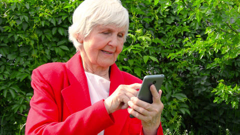 portrait of old lady, grandmother use phone outdoors at sun day. modern granny Footage