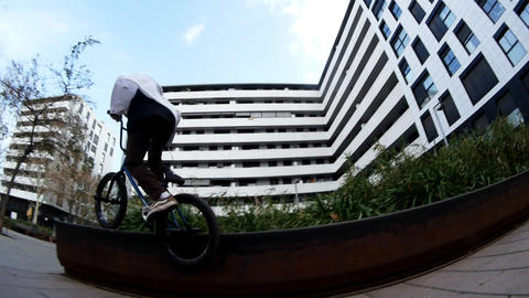 Skilled guy BMX rider in orange cap practices jumps and spins in urban space Live Action
