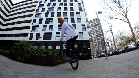 Slim skilled guy BMX rider practices jumps and spins on bike in urban space Live Action