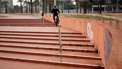 Extremal guy rides on bike and jumps over cascade brick stairs and handrails Footage