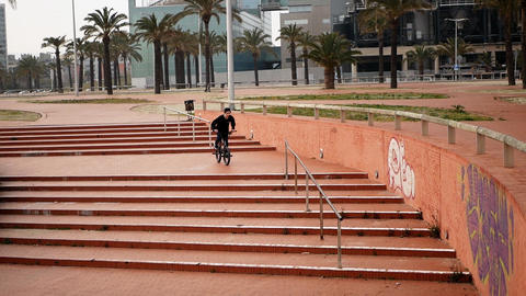 Active young man rides on bike and jumps over cascade brick stairs and handrails Footage