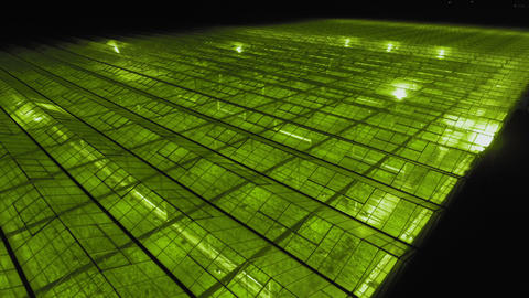 Aerial - Exterior shot of greenhouse with LED lights on for growing plants Footage