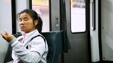 Asian woman wearing white sportive shirt sits in moving train and looks around Live Action