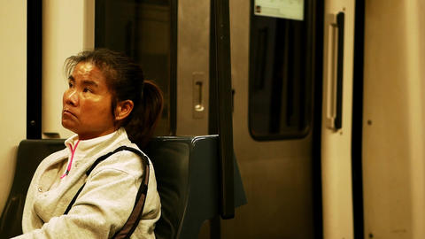 Asian woman with tired look in white sportive shirt sits in moving train Live Action