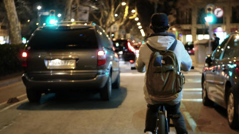 Young men friends cyclists are moving along narrow road with cars in street Live Action