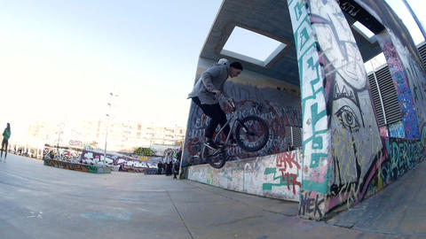 Man BMX rider makes different spins and tricks on bike in urban environment Live Action