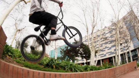 Young skilled man bicycler is riding and jumping on retaining brick wall curb Live Action
